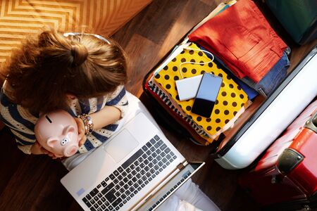 Upper view of young woman in white pants and striped blouse in the modern living room in sunny summer day holding piggy bank near open travel suitcase planning budget summer trip.