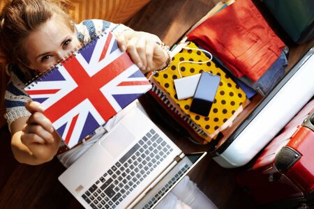 Upper view of stylish woman in white pants and striped blouse at modern home in sunny summer day showing Great Britain flag notebook while booking hotel online near open travel suitcase. Stok Fotoğraf - 124780744