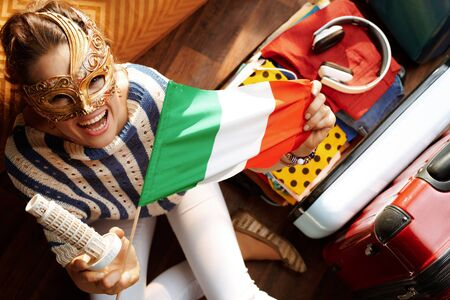 Upper view of smiling woman in white pants and striped blouse at modern home in sunny summer day wearing Venice mask showing Italian flag and leaning tower of Pisa souvenir near open travel suitcase. Stok Fotoğraf