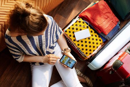 Upper view of stylish woman in white pants and striped blouse in the modern house in sunny summer day book flight on phone near open travel suitcase.