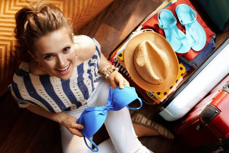 Upper view of elegant woman in white pants and striped blouse in the modern living room in sunny summer day packing bikini in open travel suitcase. Stok Fotoğraf - 124780749