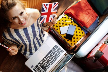 Upper view of smiling young woman in white pants and striped blouse with Great Britain flag notebook buying airplane ticket near open travel suitcase in the modern house in sunny summer day.