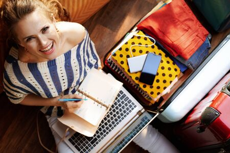 Upper view of happy stylish woman in white pants and striped blouse in the modern living room in sunny summer day planning holiday online near open travel suitcase.