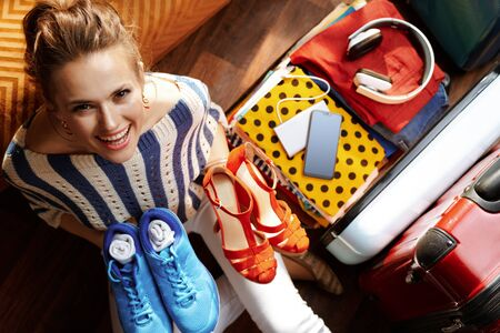 Upper view of smiling modern woman in white pants and striped blouse in the modern house in sunny summer day packing glamorous and comfortable shoes near open travel suitcase.