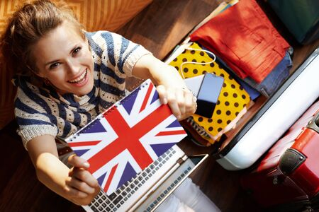 Upper view of happy modern woman in white pants and striped blouse in the modern living room in sunny summer day showing Great Britain flag notebook while buying ticket near open travel suitcase.