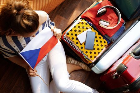 Upper view of elegant woman in white pants and striped blouse with Czech flag near open travel suitcase at modern home in sunny summer day. Stok Fotoğraf - 124780755