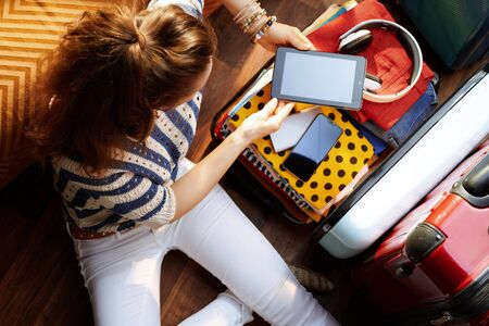 Upper view of stylish woman in white pants and striped blouse in the modern living room in sunny summer day packing electronic stuff in open travel suitcase.