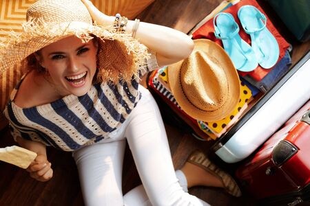 Upper view of smiling stylish woman in white pants and striped blouse with big summer hat near open travel suitcase eating ice cream packing for summer vacation at modern home in sunny summer day.