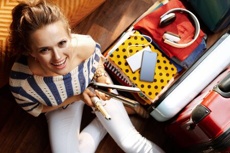 Upper view of smiling modern woman in white pants and striped blouse in the modern house in sunny summer day packing hair curler and iron in open travel suitcase. Stok Fotoğraf - 124780759