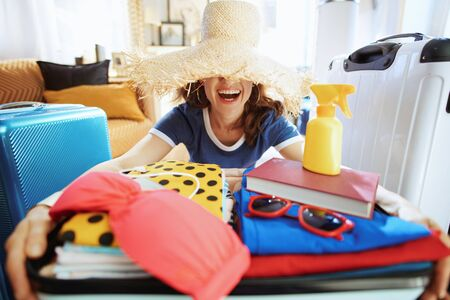 young traveller woman in blue t-shirt in the modern house in sunny summer day wearing big beach straw hat. Stock fotó
