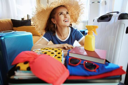 pensive elegant tourist woman in blue t-shirt with big beach straw hat preparing for summer trip at modern home in sunny summer day.