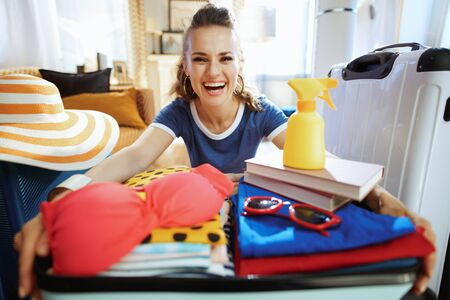 smiling modern woman in blue t-shirt with open suitcase ready for resort in the modern living room in sunny summer day.