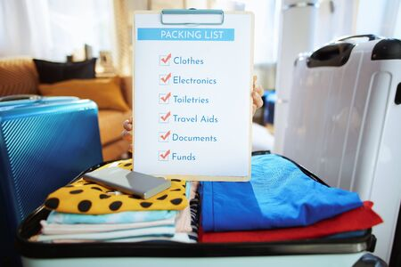 Closeup on young traveller woman in blue t-shirt at modern home in sunny summer day showing packing list.
