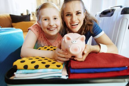 Portrait of smiling young mother and child in the modern living room in sunny summer day showing piggy bank.