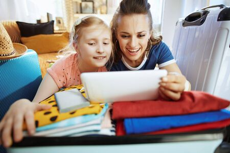 happy trendy mother and child travellers at modern home in sunny summer day booking hotel room online using mobile app on tablet PC. Stock Photo