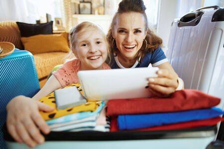 smiling young mother and daughter tourists in the modern house in sunny summer day buying flights online using mobile app on tablet PC. Stock Photo
