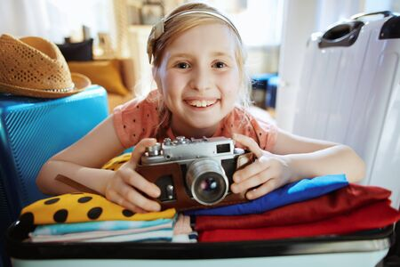 smiling young traveller girl with retro film camera packing suitcase at modern home in sunny summer day. Stock Photo - 125216622