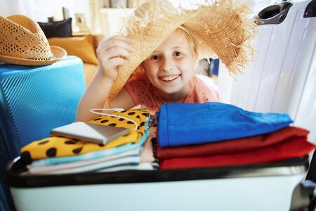 smiling young traveller girl with big beach straw hat packing for summer travel in the modern living room in sunny summer day.