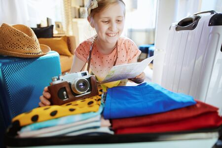 happy modern tourist girl with retro film camera and map with open suitcase ready for vacation in the modern living room in sunny summer day. Stock Photo