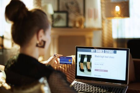 Over shoulder shot of trendy woman in black blouse with credit card buying shoe while shop online sitting on divan in the modern house in sunnny hot summer day.