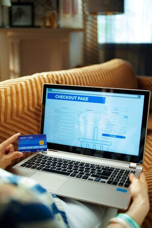 housewife with credit card finishing online shop process on a laptop while sitting on sofa at modern home in sunny hot summer day. Banque d'images - 129554690