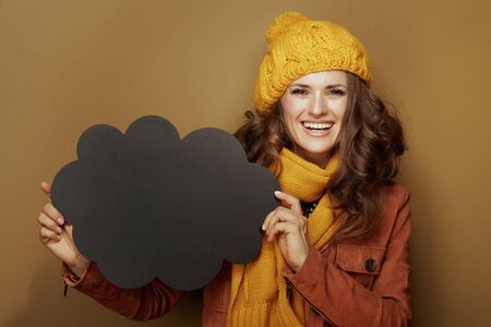 Hello autumn. Portrait of 40 year old woman in yellow beret and scarf showing cloud shape blank blackboard on beige background.