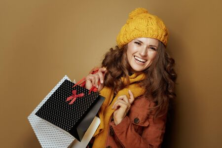 Hello autumn. Portrait of smiling young woman in yellow beret and scarf with shopping bags against brown background.