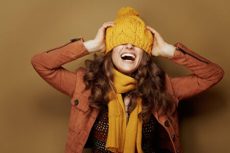 Hello autumn. cheerful elegant woman in yellow scarf with beret over eyes on beige background.