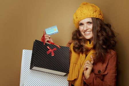 Hello autumn. 40 year old woman in yellow beret and scarf with credit card and shopping bags on brown background.