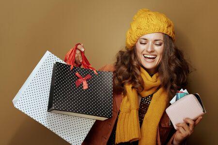 Hallo herfst. gelukkige jonge vrouw in gele baret en sjaal met creditcard, portemonnee en boodschappentassen geïsoleerd op beige.