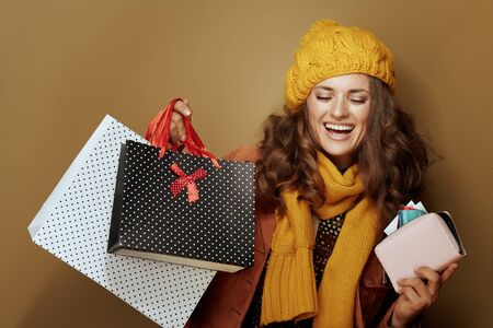 Hello autumn. happy young woman in yellow beret and scarf with credit card, purse and shopping bags isolated on beige.