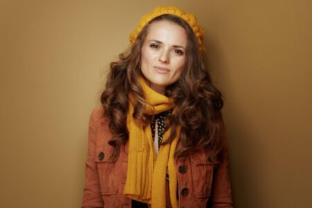 Hello autumn. Portrait of middle age woman in yellow beret and scarf against brown background. Reklamní fotografie