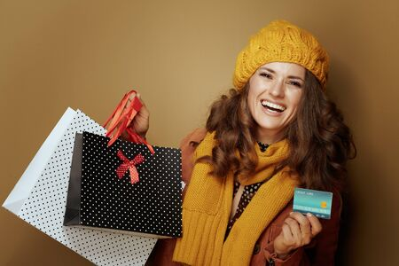 Hello autumn. happy stylish woman in yellow beret and scarf with credit card and shopping bags against beige background.