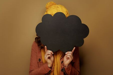 Hello autumn. modern woman in yellow beret and scarf hiding behind cloud shape blank blackboard on beige background.