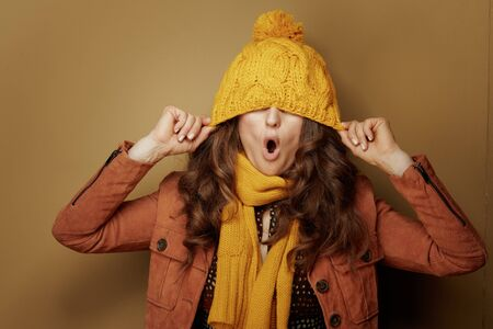 Hello autumn. cheerful stylish woman in yellow scarf with a beret over eyes on brown background.