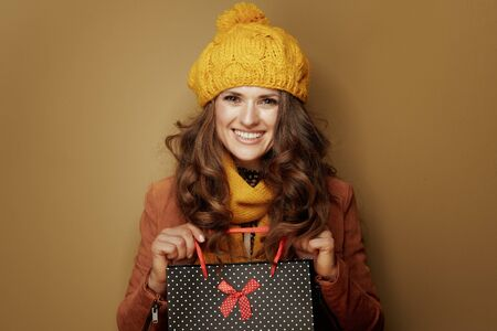 Hello autumn. Portrait of smiling modern woman in yellow beret and scarf showing black dotted shopping bag isolated on beige background. Reklamní fotografie