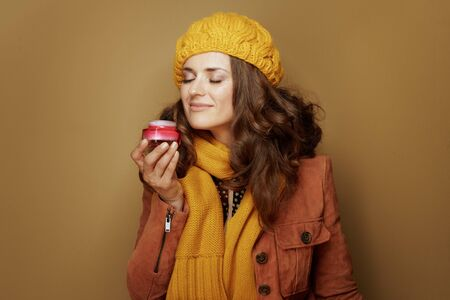 Hello autumn. stylish woman in yellow beret and scarf enjoying facial creme fragrance isolated on beige.