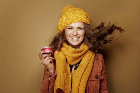 Hello autumn. Portrait of cheerful elegant woman in yellow beret and scarf with jar of facial creme on bronze background.