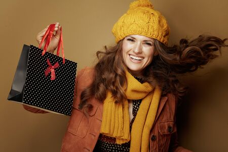 Hello autumn. Portrait of cheerful trendy woman in yellow beret and scarf showing black dotted shopping bag isolated on beige background.