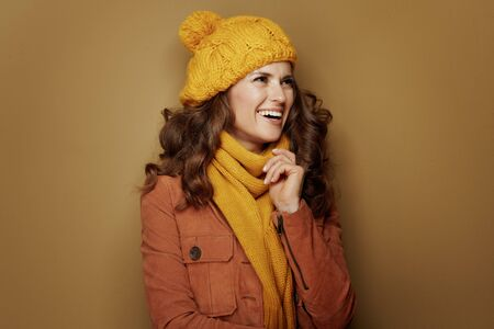 Hello autumn. happy elegant woman in yellow beret and scarf looking aside isolated on beige. Reklamní fotografie