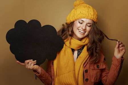 Hello autumn. smiling elegant woman in yellow beret and scarf showing cloud shape blank blackboard on bronze background. Reklamní fotografie