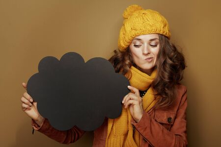 Hello autumn. Portrait of doubting elegant woman in yellow beret and scarf looking at cloud shape blank blackboard isolated on beige.