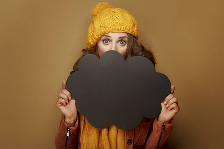 Hello autumn. surprised stylish woman in yellow beret and scarf hiding behind cloud shape blank blackboard against brown background.