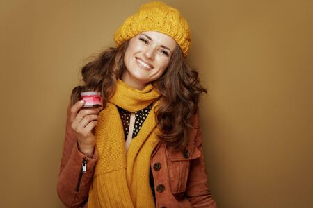 Hello autumn. Portrait of smiling young woman in yellow beret and scarf with jar of facial creme isolated on bronze background.