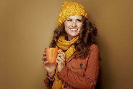 Hello autumn. 40 year old woman in yellow beret and scarf with cup of cappuccino isolated on beige. Reklamní fotografie