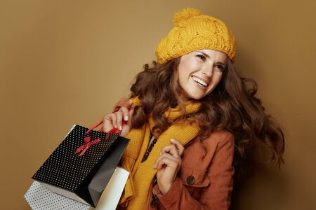 Hello autumn. cheerful stylish woman in yellow beret and scarf with shopping bags isolated on brown background.