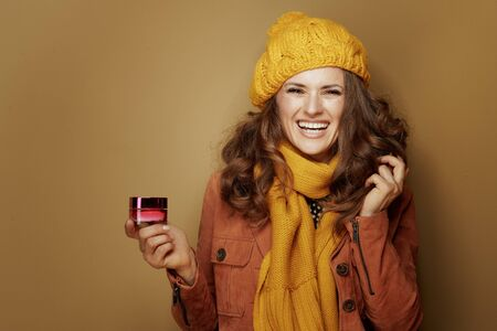 Hello autumn. Portrait of happy stylish woman in yellow beret and scarf with jar of facial creme isolated on bronze background.