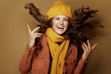 Hello autumn. Portrait of happy stylish woman in yellow beret and scarf jumping on bronze background.