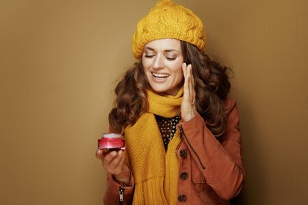 Hello autumn. 40 year old woman in yellow beret and scarf using facial creme against beige background.