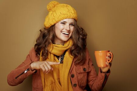 Hello autumn. smiling modern woman in yellow beret and scarf pointing at cup of pumpkin latte against bronze background.